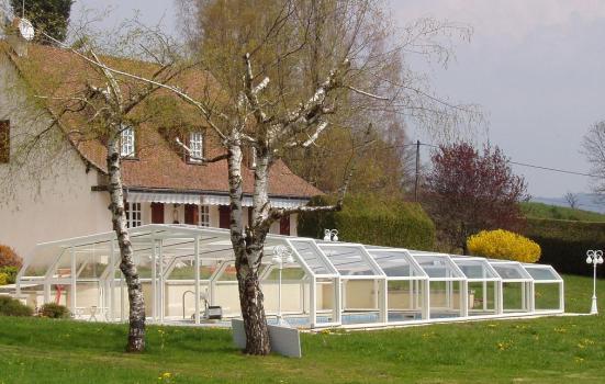 Abri piscine télescopique intermédiaire VENUS en 5 angles blanc face à la maison